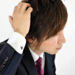 スーツ姿で頭を掻く人