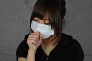 マスクで咳払いする女性